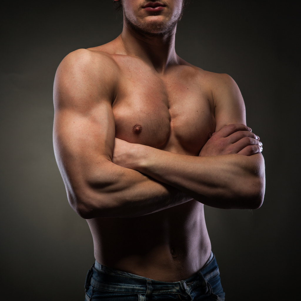 shirtless muscular man with black backdrop