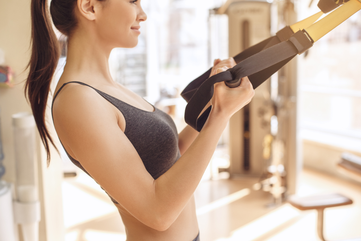 Young woman using exercise for sagging breasts in the gym